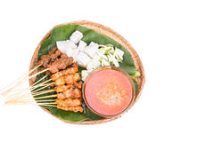 Barbecue satay served on traditional rattan plate with banana le Stock Images