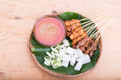 Barbecue satay served on traditional rattan plate with banana le Royalty Free Stock Images