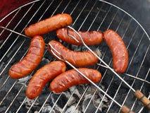 Barbecue, saucisses et pinces Photographie stock libre de droits