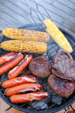 Barbecue of sausage, steak, and corn Stock Photo