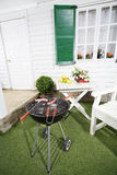 Barbecue with sausages, table with fruits and flowers Royalty Free Stock Image