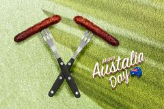 Barbecue sausages on two forks with Happy Australia Day text royalty free stock image