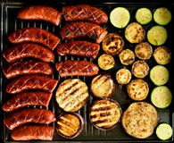 Barbecue. Sausages and vegetables on the grill Stock Photography
