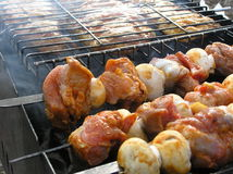 Barbecue and shashlik. Grilled meat and mushrooms (barbecue and shashlik). Shashlik (sort of barbecue Stock Photos