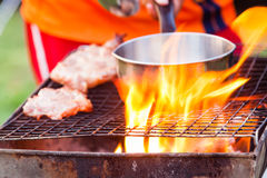 Barbecue in a simple way in wild, collect stones as grill. Outdoor charcoal grilled pork. collect stones as grill royalty free stock photography
