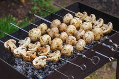 Barbecue skewers with grilled champignon mushroom kebab in a brazier Stock Photo