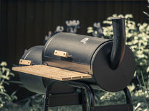 Barbecue with smoke pipe in the summer garden of cottage. Cylindrical black barbecue with smoke pipe and smoke box in the summer garden of cottage Royalty Free Stock Photos