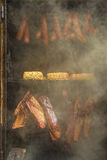 Barbecue smoker. Indian corn, homemade sausages, cheese and ham in barbecue smoker stock photography