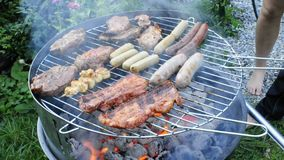 Barbecue. Smoking and burning charcoal and meat and sausages on the grid with people turning it stock footage