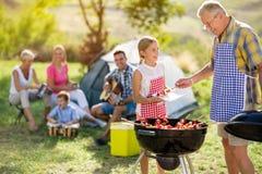 Barbecue sorridente di cottura della nipote con il nonno Immagine Stock Libera da Diritti