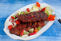 Barbecue spare ribs from a grill with vegetables Stock Images