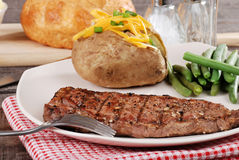 Barbecue steak with baked potato and cheese. Closeup Barbecue steak with baked potato and cheese Royalty Free Stock Image