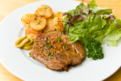 Barbecue with steaks of pork,fried potatoes,salad Royalty Free Stock Photography
