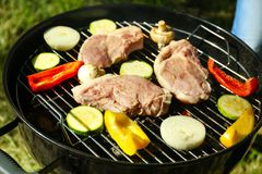 Barbecue steaks with vegetables. On grill outdoors Royalty Free Stock Photography
