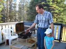 Barbecue on the sundeck. Father and daughter getting ready to eat outside Royalty Free Stock Photography