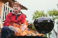 Barbecue time. European man in hat waiting for grilled food. He is sitting near fire and rest stock image