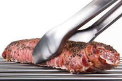 Barbecue tongs grabs a big portion of roast pork, isolated on wh Stock Image