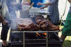 Barbecue turkey legs on the grill. With smoke at a festival Royalty Free Stock Images
