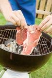 Barbecue: Uomo che pone bistecca nella lombata sulla griglia Immagini Stock Libere da Diritti