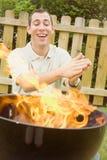 Barbecue: Uomo eccitato dalle alte fiamme del BBQ Fotografie Stock
