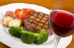 Barbecued Beef Steak and a Glass of Red Wine #2. Barbecued rib eye steak served with vegetables and a glass of red wine, #2 royalty free stock photography