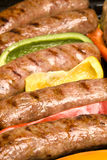 Barbecued bratwurst. A row of grilled, barbecued bratwurst with bell pepper garnish ready to serve. Focus is selective on the second to the front brat royalty free stock photo