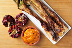Barbecued calcots, sweet onions, and romesco sauce typical of Ca. Closeup of a plate with barbecued calcots, sweet onions, and a bowl with romesco sauce, typical stock image