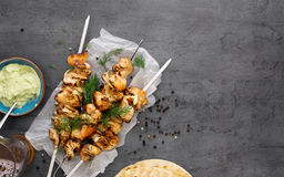 Barbecued chicken breast skewers with flat bread and avocado sauce. Top view barbecued chicken breast skewers with flat bread and avocado sauce on dark royalty free stock photo
