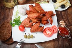 Barbecued chicken drumsticks and vegetables.  stock photo