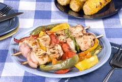 Barbecued chicken kebab. A barbecued chicken kebab dinner with corn on the cob on a picnic table setting stock photo
