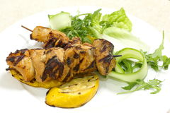 Barbecued chicken kebabs. Served with a salad and viewed from the side stock photography