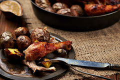 Barbecued chicken leg with baked potatoes Stock Photography