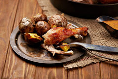 Barbecued chicken leg with baked potatoes Royalty Free Stock Images