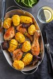 Barbecued chicken leg with boiled potatoes and vegetables on black background. Copy space. Top view. Barbecued chicken leg with boiled potatoes and vegetables royalty free stock image