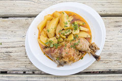Barbecued chicken leg with boiled potatoes. On wooden table Stock Images