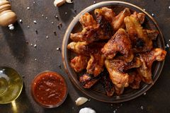 Barbecued chicken wings with bbq sauce on the plate. Top view with copy space stock photo