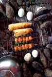 Barbecued food - eggs, mutton, sweet potatoes and corns. Hard-boiled eggs, corns on a cob, sweet potatoes and sticks of mutton, barbecued food sold at a street stock photo