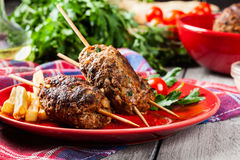 Barbecued kofta with fries on a plate. Selective focus stock photos