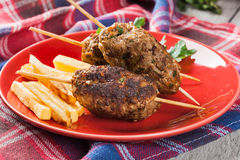 Barbecued kofta with fries on a plate Stock Image