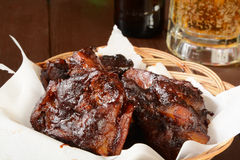 Barbecued pork ribs. Closeup of a basket of barbecued pork ribs on bar counter with a mug of beer royalty free stock images