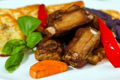 Barbecued pork ribs with fried potato pancakes, served with basil, grilled carrots and paprika. Restaurant menu photo stock images
