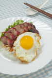 Barbecued pork with rice and omelette. On the blue checkered tablecloth Stock Image