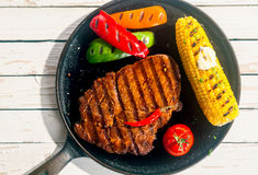 Barbecued rib eye beef steak with corn on the cob. Barbecued rib eye beef steak with grilled corn on the cob, colorful peppers and a tomato, served on a skillet stock image