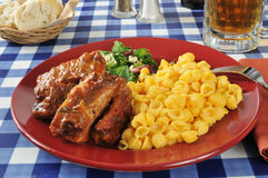 Barbecued ribs with macaroni and cheese. And a green salad royalty free stock images