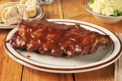 Barbecued ribs with potato salad. And a dinner roll royalty free stock image
