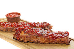 Barbecued ribs with sauce on cutting board. Royalty Free Stock Images