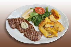Barbecued rump steak with herb butter,fried potatoes. And mache,close-up Royalty Free Stock Image