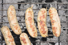 Barbecued sausages. Gourmet sausages cooking on a barbecue Stock Images