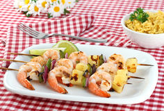 Barbecued Shrimp Kabobs. Three skewers of barbecued shrimp, peppers, onion and pineapple. Red checked picnic tablecloth, daisies, and a side of rice stock image