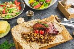 Barbecued spare ribs, buckwheat with mushroom and tomatoes on old wooden cutting board and salats Royalty Free Stock Image